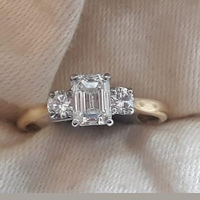 Emerald cut and 2 round diamonds. White gold claws and yellow gold shank.